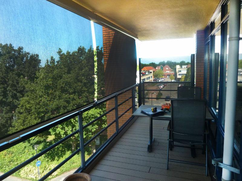 Uitschuifbaar windscherm. Horizontaal geplaatst en verticaal te bedienen. Ideaal voor balkon.